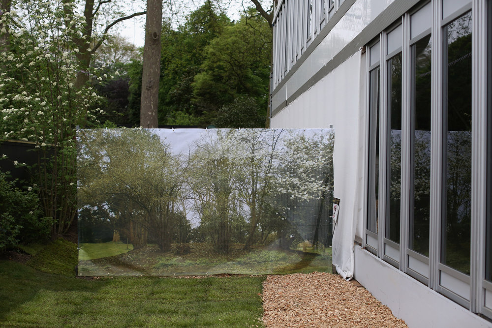 . A screen depicting a garden scene is erected next to a temporary marquee at the RHS Chelsea Flower Show on May 21, 2013 in London, England. The Chelsea Flower Show run by the RHS celebrates its 100th birthday this year.  (Photo by Oli Scarff/Getty Images)