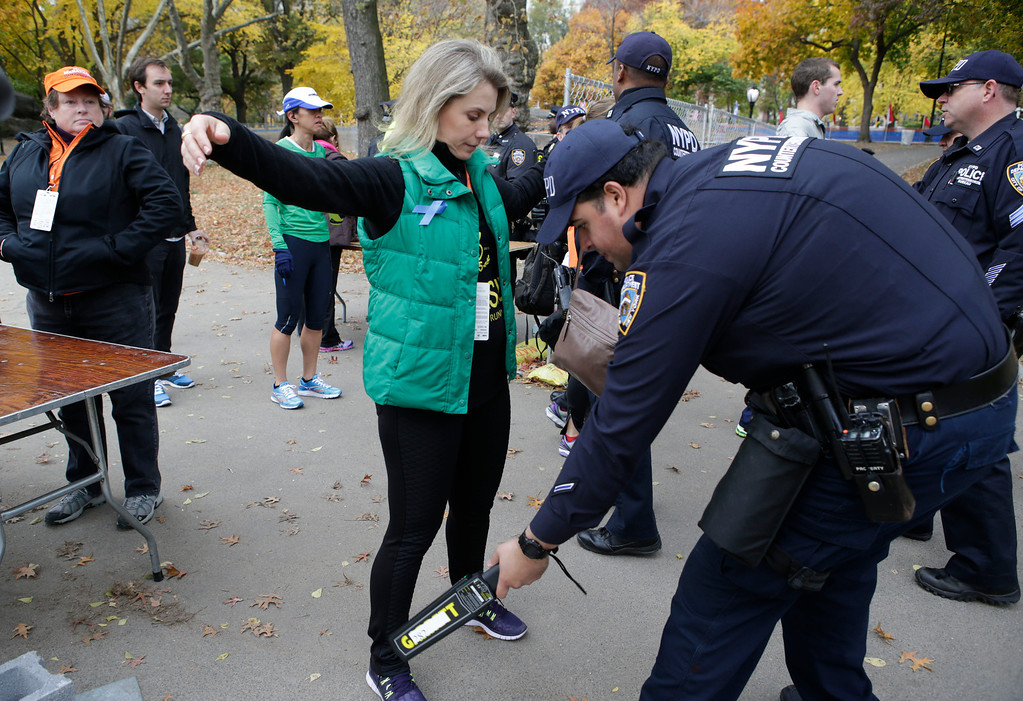 . A counterterrorism police officer uses a metal detecting wand at a security checkpoint near the finish line of the 2013 New York City marathon, Sunday, Nov. 3, 2013, in New York. Increased security is visible in the wake of the Boston Marathon bombings. (AP Photo/Kathy Willens)