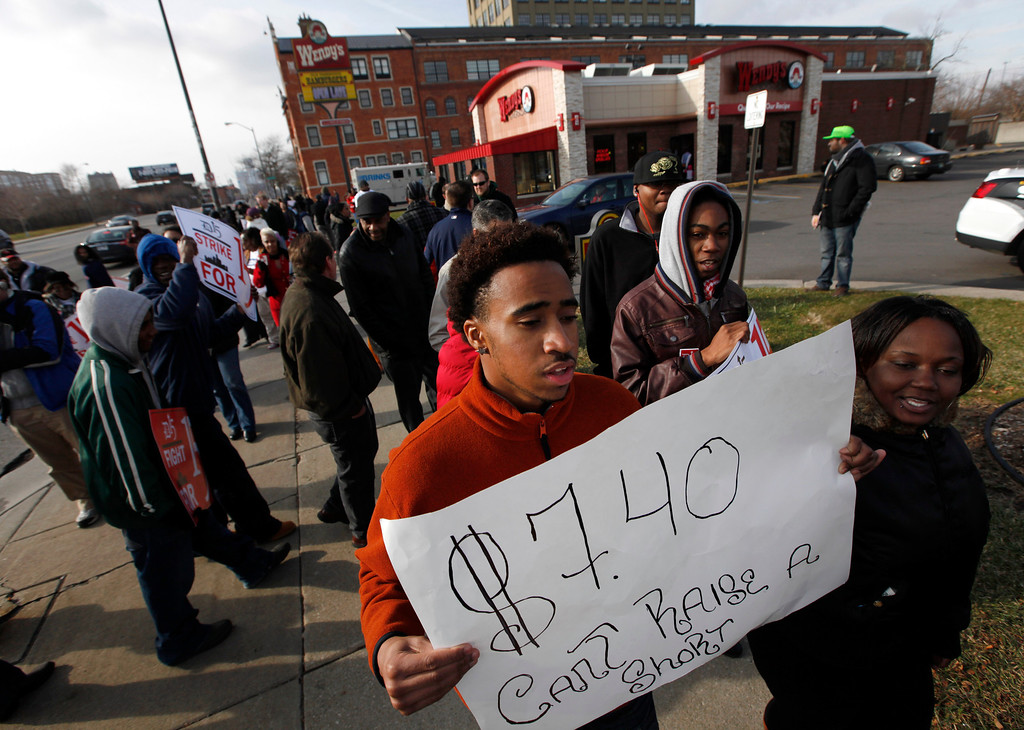 . Protester Austin Prude holds a sign during a rally for better wages at a Wendy\'s in Detroit Thursday, Dec. 5, 2013.  (AP Photo/Paul Sancya)
