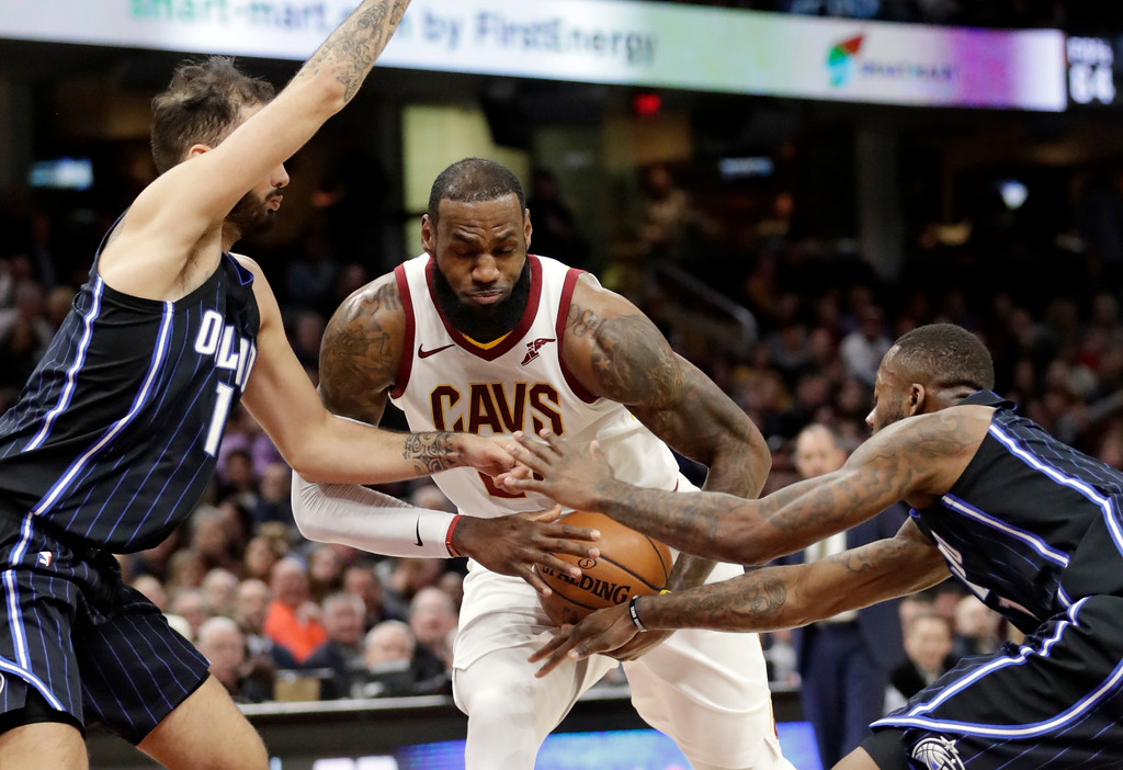 . Cleveland Cavaliers\' LeBron James, center, drives between Orlando Magic\'s Evan Fournier, left, and Orlando Magic\'s Jonathon Simmons during the first half of an NBA basketball game Thursday, Jan. 18, 2018, in Cleveland. (AP Photo/Tony Dejak)