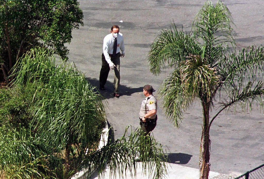 Description of . A police investigator with his face and hands covered, walks in Rancho Santa Fe, California on March 27, 1997 near the house where 39 people were found dead in what is being described as a mass suicide. The bodies were found inside a rented million-dollar-plus estate and a San Diego Sheriff's Department Lieutenant Jerry Lipscomb said the deaths were due to an overdose of drugs. HECTOR MATA/AFP/Getty Images