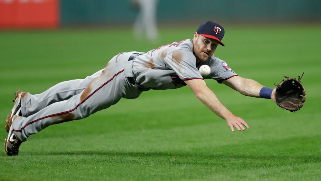 . Minnesota Twins\' Logan Forsythe dives for the ball hit by Cleveland Indians\' Michael Brantley during the sixth inning of a baseball game Tuesday, Aug. 7, 2018, in Cleveland. Brantley was safe at first base. (AP Photo/Tony Dejak)