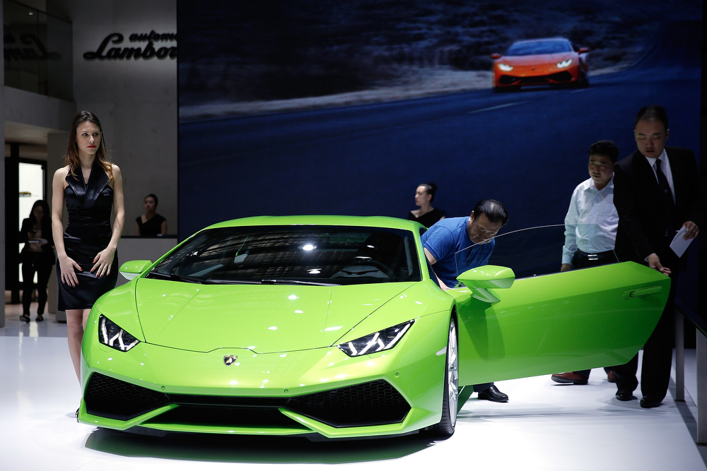 . People look at a Lamborghini sport car during the 2014 Beijing International Automotive Exhibition at China International Exhibition Center on April 22, 2014 in Beijing, China. More than 2,000 automotive enterprises from 14 countries and regions participated in the 2014 Beijing International Automotive Exhibition from April 20 to April 29.  (Photo by Lintao Zhang/Getty Images)