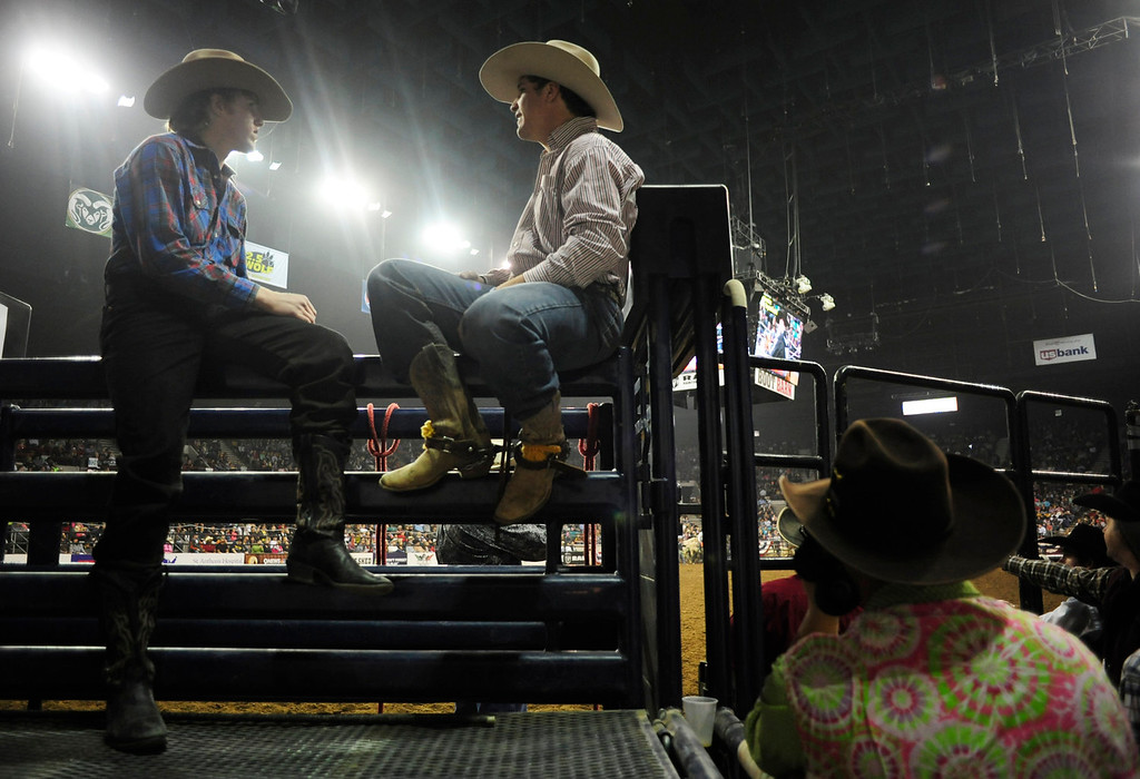 . Brady Portenier (left), of Caldwell, ID, sits alongside the ring with fellow bull riding contestant Garrett Smith (right), of Rexburg, ID, before their competition begins, during the U.S. Bank Pro Rodeo Finals, at the National Western Stock Show in Denver, CO, Sunday, January 26, 2014. Sunday was the final day of the event. (Photo By Brenden Neville / Special to The Denver Post)