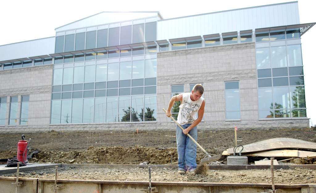. Jerry Boso, an employee at Carson Concrete out of North Canton, prepares the ground to have concrete poured for a sidewalk in front of the new Holden University Center in September 2011. (News-Herald file)
