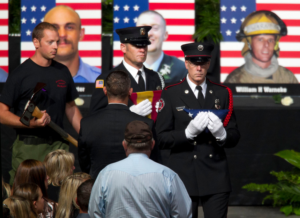 . Firefighters present American flags, Arizona flags and Pulaskis to family members of the fallen firefighters during a memorial service for the 19 fallen firefighters at Tim\'s Toyota Center in Prescott Valley, Ariz. on Tuesday, July 9, 2013.   (AP Photo/The Arizona Republic, Michael Chow, Pool)