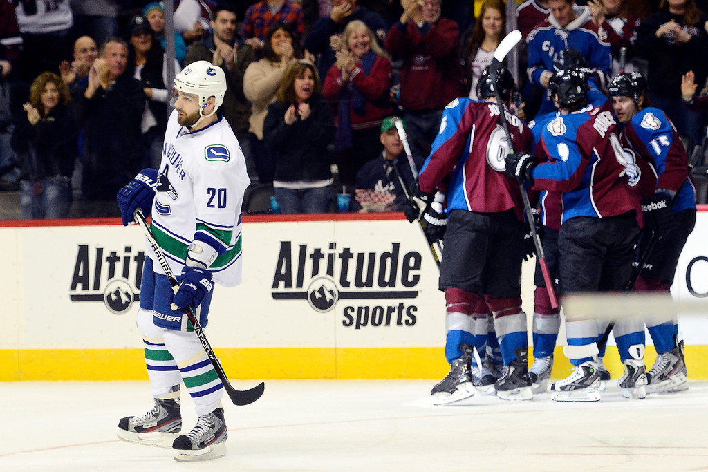 . DENVER, CO - MARCH 24: Jamie McGinn (11) of the Colorado Avalanche celebrates his 1-1 goal as Chris Higgins (20) of the Vancouver Canucks reacts during the first period of action. Colorado Avalanche versus the Vancouver Canucks at the Pepsi Center. (Photo by AAron Ontiveroz/The Denver Post)