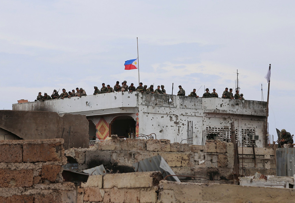 . The Philippine national flag flies at half-staff as soldiers watch a news conference below of top Government officials at the site of a three-week intense fighting between Government forces and Muslim rebels who have taken nearly 200 people hostages, in Zamboanga city, southern Philippines, Saturday Sept. 28, 2013. The deadly standoff between government troops and Muslim rebels has ended with all of the captives safe, officials said Saturday. Defense Secretary Voltaire Gazmin said only a handful of Moro National Liberation Front rebels remained in hiding and were being hunted by troops in the coastal outskirts of the city, adding authorities were trying to determine if rebel commander Habier Malik, who led the Sept. 9 siege, was dead. More than 200 people were killed in the clashes, including 183 rebels and 23 soldiers and police, in one of the bloodiest and longest-running attacks by a Muslim group in the south, scene of decades-long Muslim rebellion for self-rule in the largely Roman Catholic country. (AP Photo)