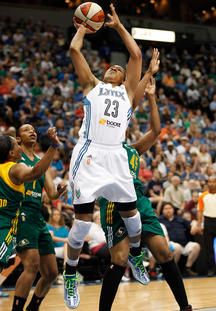 . Minnesota Lynx forward Maya Moore (23) pushes through Seattle Storm guard Noelle Quinn (45) for a basket in the first half of a WNBA basketball game, Sunday, Aug. 4, 2013, in Minneapolis. (AP Photo/Stacy Bengs)