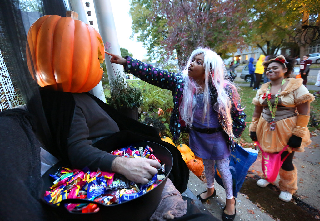 """. Thaileah Winfrey, 10, of Dubuque, Iowa, gets a closer look of Terry Kosel, dressed as the \""""Great Pumpkin,\"""" while trick-or-treating along South Grandview Avenue Thursday, Oct. 31, 2013, in Dubuque, Iowa. (AP Photo/Telegraph Herald, Jessica Reilly)"""