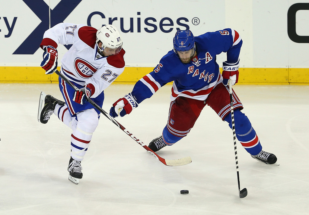 . Dan Girardi #5 of the New York Rangers battles for the puck against Alex Galchenyuk #27 of the Montreal Canadiens in Game Three of the Eastern Conference Final during the 2014 NHL Stanley Cup Playoffs at Madison Square Garden on May 22, 2014 in New York City.  (Photo by Elsa/Getty Images)