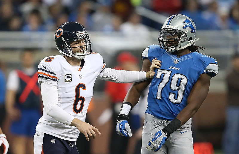 . Jay Cutler #6 of the Chicago Bears gives Willie Young #79 of the Detroit Lions a push during the game at Ford Field on December 30, 2012 in Detroit, Michigan. The Bears defeted the Lions 26-24.  (Photo by Leon Halip/Getty Images)