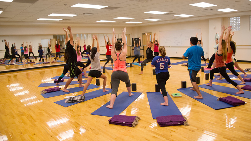 Instructor Lindy Burns leads students through basic steps in Yoga class.