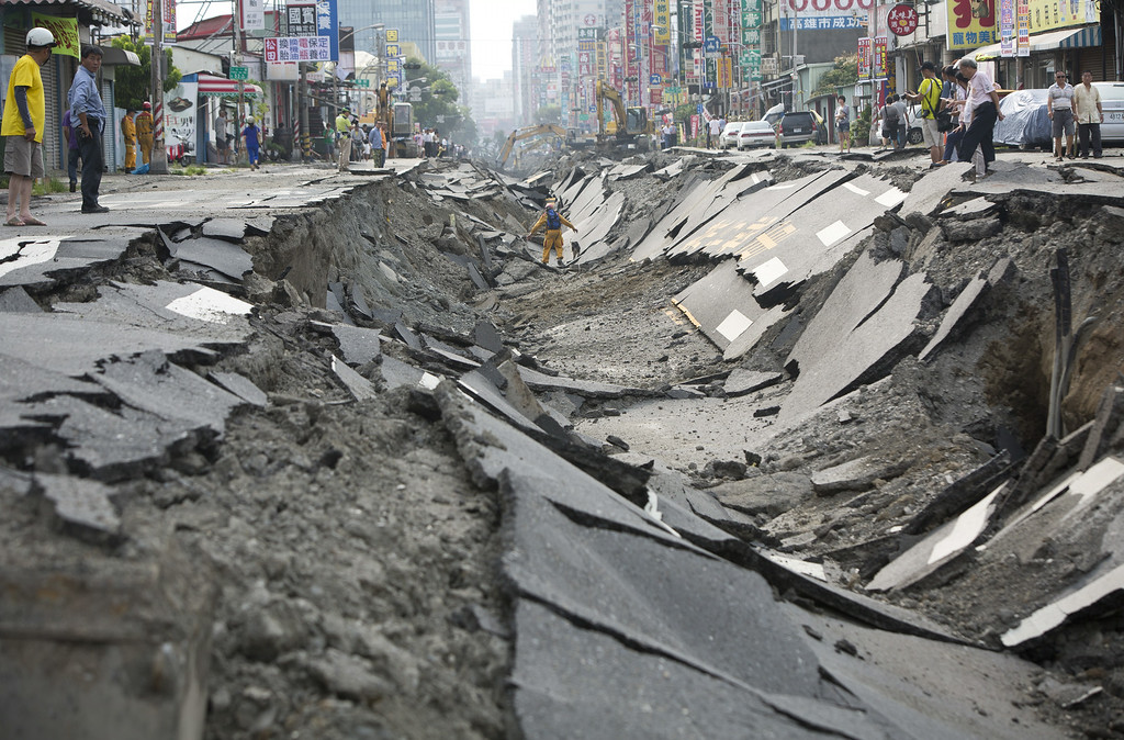 . Rescue workers stand in the damaged road after gas explosions in southern Kaohsiung on August 1, 2014 in Kaohsiung, Taiwan. A series of powerful gas blasts killed 25 people and injured up to 267 in the southern Taiwanese city of Kaohsiung, overturning cars and ripping up roads, officials said.  (Photo by Ashley Pon/Getty Images)