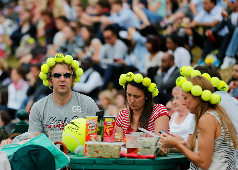 . Spectators watch Petra Kvitova of Czech Republic on a large video screen as she wins the women\'s singles final against Eugenie Bouchard of Canada at the All England Lawn Tennis Championships in Wimbledon, London Saturday, July 5, 2014. (AP Photo/Ben Curtis)