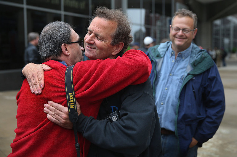 . Former Chicago Sun-Times photographers Scott Stewart (L), Rich Chapman (C), and Matt Marton greet each other following a demonstration outside the offices of the Sun-Times on June 6, 2013 in Chicago, Illinois. Union members, reporters, and photographers gathered outside the newspaper\'s office to protest the company\'s decision last week to eliminate its 28-member photo staff. The newspaper chain plans to train their reporters to take pictures with iPhones to fill the void.  (Photo by Scott Olson/Getty Images)