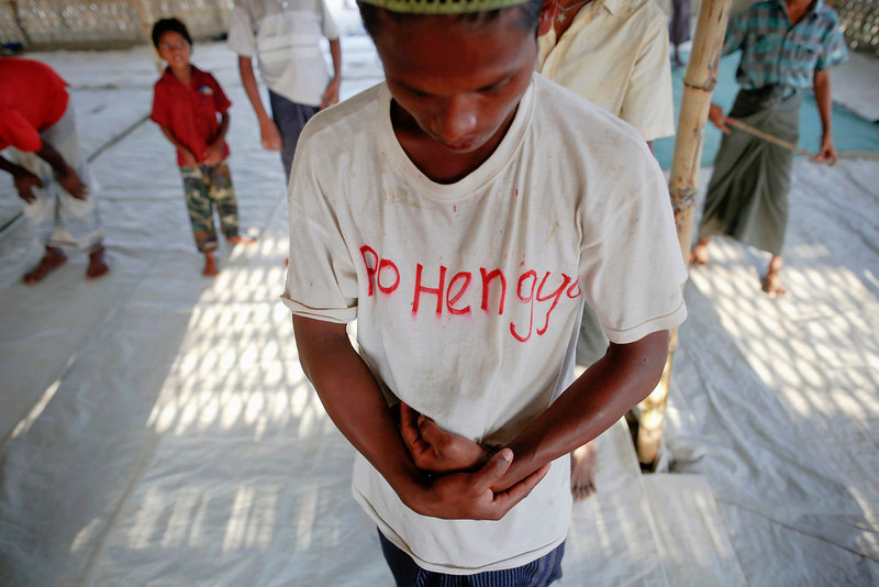 ". A Rohingya Muslim with the word ""Rohingya\"" written on his T-shirt prays with others in a makeshift mosque at a camp for those displaced by violence, near Sittwe April 28, 2013. Myanmar must urgently address the plight of Muslims displaced by sectarian bloodshed in western Rakhine State and double the number of security forces to control the still-volatile region, an independent commission said on Monday. Its long-awaited report recommended a mixed bag of humanitarian and security responses to violence last June and October that killed at least 192 people and left 140,000 homeless, mostly stateless Rohingya Muslims in an area dominated by ethnic Rakhine Buddhists. Picture taken April 28, 2013.  REUTERS/Damir Sagolj"