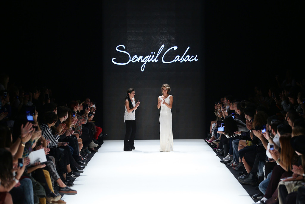 . Fashion designer Songul Cabaci (L) and a model walk the runway at the Songul Cabaci show during Mercedes-Benz Fashion Week Istanbul s/s 2014 presented by American Express on October 9, 2013 in Istanbul, Turkey.  (Photo by Vittorio Zunino Celotto/Getty Images for IMG)