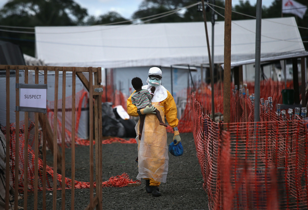 . A Doctors Without Borders (MSF), health worker in protective clothing carries a child suspected of having Ebola in the MSF treatment center on October 5, 2014 in Paynesville, Liberia. The girl and her mother, showing symptoms of the deadly disease, were awaiting test results for the virus. The Ebola epidemic has killed more than 3,400 people in West Africa, according to the World Health Organization.  (Photo by John Moore/Getty Images)