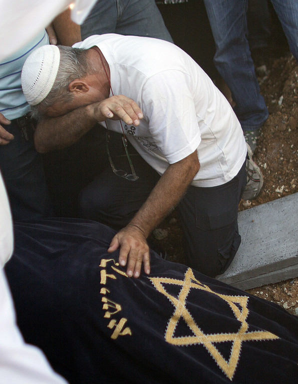 . A relative of Dror Khenin grieves on July 16, 2014, during his funeral in Yehud, east of Tel Aviv, the day after he was killed when a short-range rocket fired by Palestinian militants landed near the border with the Gaza Strip where he was delivering food to the Israeli soldiers. He is the first Israeli civilian killed during Israel\'s Operation Dove. Israel\'s campaign, now in its ninth day, has killed 214 Palestinians, with a Gaza-based rights group saying over 80 percent of them were civilians. AFP PHOTO/AHMAD  GHARABLI/AFP/Getty Images