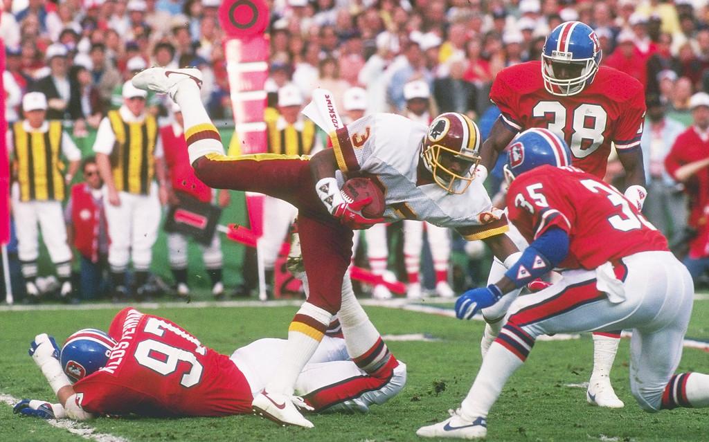 . Wide receiver Ricky Sanders of the Washington Redskins attempting to avoid several Denver Broncos defenders during Super Bowl XXII at Jack Murphy Stadium in San Diego, California.   Mandatory Credit: Rick Stewart/Allsport