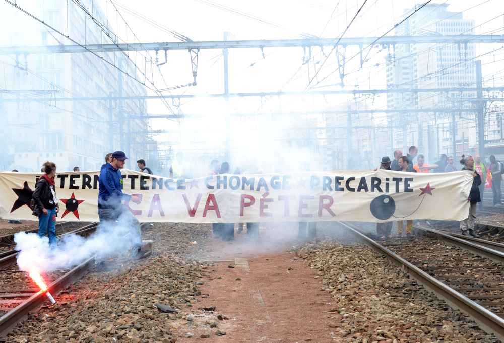 Description of . Striking workers of the French state-run rail operator SNCF, backed by French unions CGT and Sud-Rail, hold a banner reading