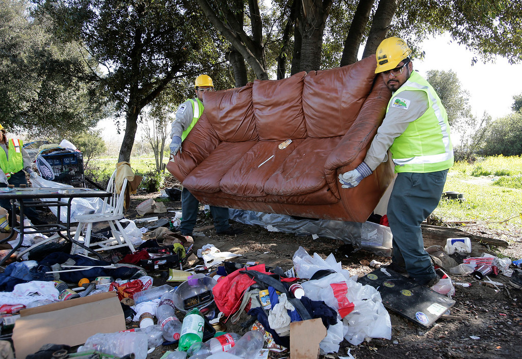 . Juan Valdez and Mario Alvarez of the San Jose Conservation Corps clean up a homeless encampment on Spring St. in San Jose, Calif. on Friday, March 8, 2013. The encampment has grown to over 100 people in the last six months. Most of the people relocated to this area after cleanup efforts took place in other parts of the city.  (Gary Reyes/ Staff)