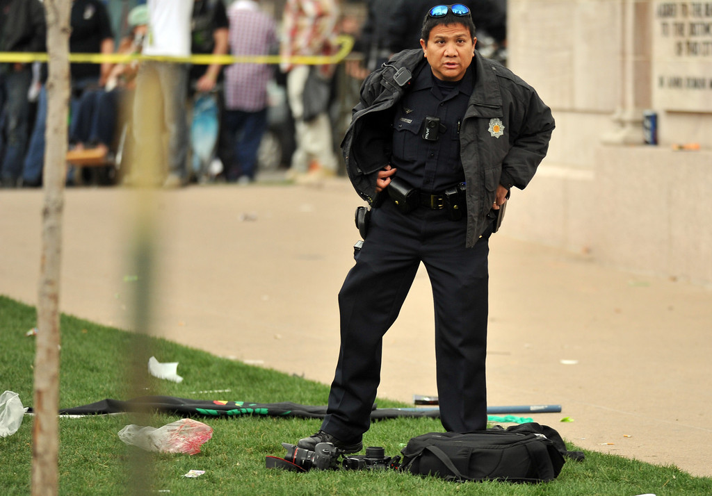 . DENVER, CO. - APRIL 20 : A Denver Police officer secures and investigating the shooting site. Two people were shot in Denver\'s Civic Center during Saturday\'s pot rally, according to paramedics on the scene. Denver, Colorado. April 20, 2013. (Photo By Hyoung Chang/The Denver Post)