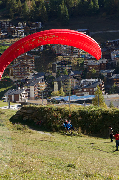 Mr. Gever and his Swiss Guide Dani getting ready to land after a paragliding adventure during Parents' Weekend
