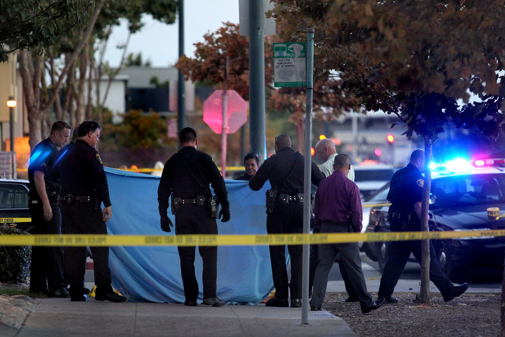 . Oakland police officers hold canvas around the 58th homicide victim as the coroners from the Alameda County Sheriff\'s Office prepare to take the body away at Mandela Parkway and 10th Street in Oakland, Calif., on Friday, Aug. 2, 2013. (Ray Chavez/Bay Area News Group)