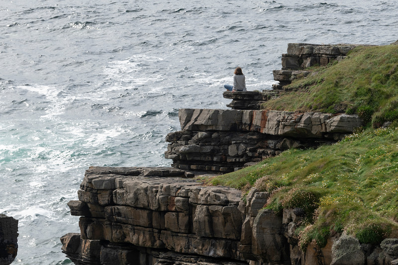 Woman sitting on the coast, Mullaghmore Peninsula, County Sligo, Ireland