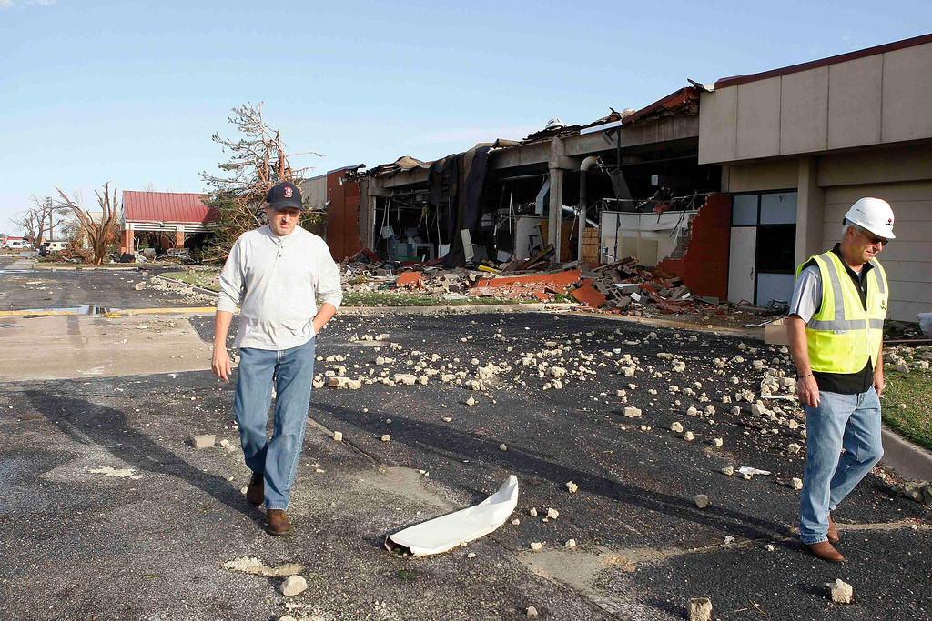 . Bill Bradley (L), assistant superintendent of the Canadian Valley Technology Center, and Cary Dehart (R) survey tornado damage at the Canadian Valley Technology Center in El Reno, Oklahoma June 1, 2013. Tornadoes killed five people in central Oklahoma including a mother and her baby and menaced Oklahoma City and its hard-hit suburb of Moore, before the storm system tracked northeast early on Saturday. REUTERS/Bill Waugh