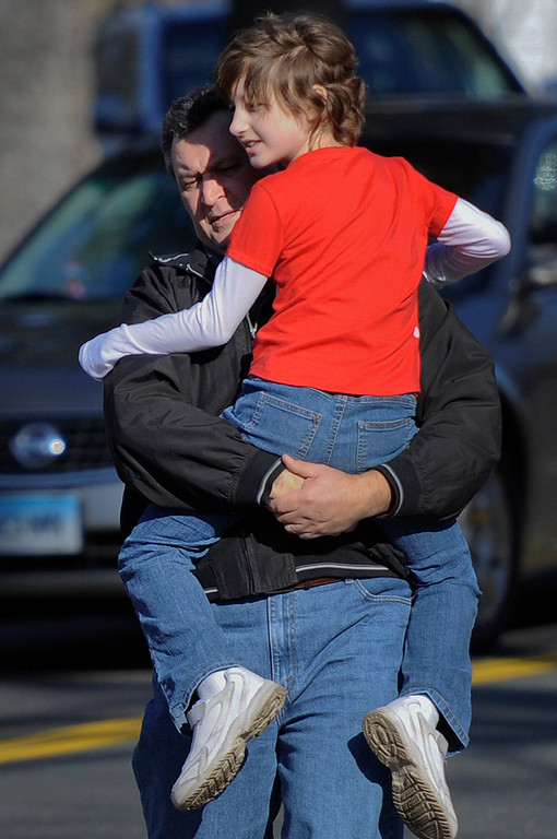 . A man carries a child away from the area of a shooting at the Sandy Hook Elementary School in Newtown, Conn., about 60 miles (96 kilometers) northeast of New York City, Friday, Dec. 14, 2012.  A man opened fire Friday inside two classrooms at the school where his mother worked as a teacher, killing 26 people, including 20 children.  The killer, armed with two handguns, committed suicide at the school and another person was found dead at a second scene, bringing the toll to 28, authorities said. A law enforcement official identified the gunman as 20-year-old Adam Lanza.  (AP Photo/Jessica Hill)