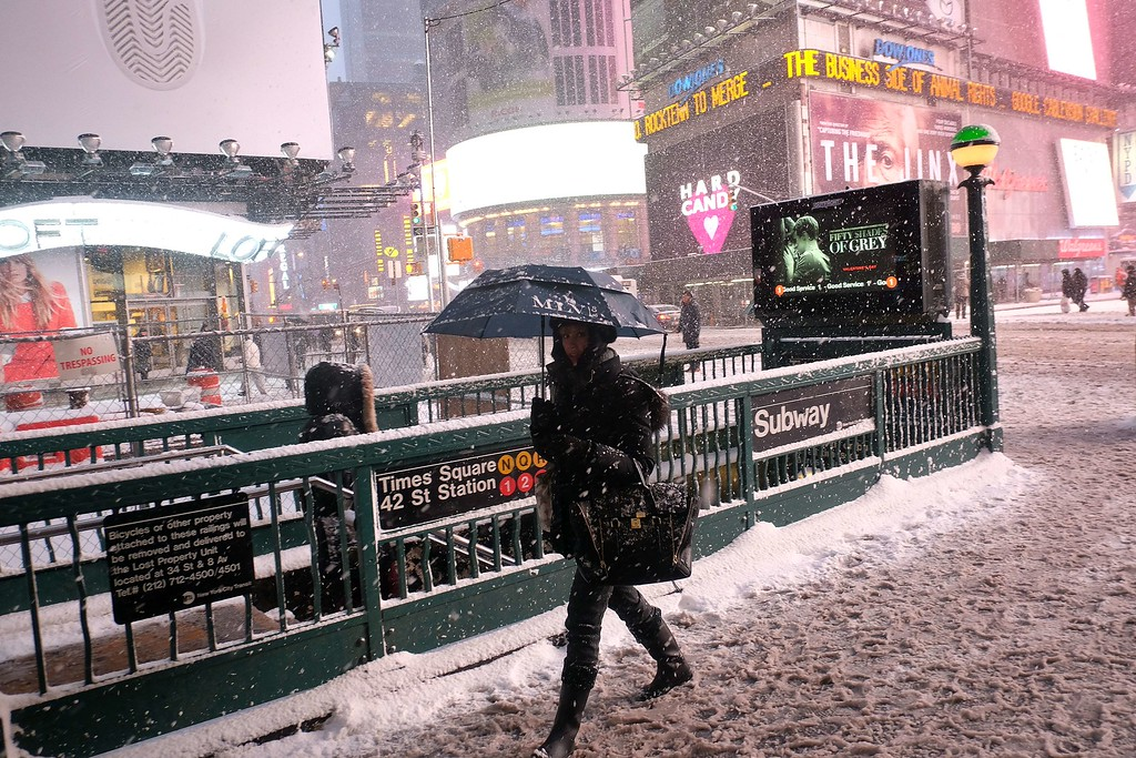 ". A woman heads to a subway station in New York\'s Times Square during a snow storm on January 26, 2015. A winter storm pounded the northeastern United US on January 26 hitting tens of millions of people and forcing the rare cancelation of Broadway shows in an ""historic\"" New York blizzard. Winter Storm Juno is expected to dump up to three feet (around a meter) of snow in parts of the northeast, with the worst affected areas likely to be New England, particularly Connecticut and Massachusetts. More than 6,560 flights on Monday and Tuesday were cancelled, the New York city transit system was to shut at 11pm and road travel made a criminal offense in 13 counties of New York state. AFP PHOTO/JEWEL SAMADJEWEL SAMAD/AFP/Getty Images"
