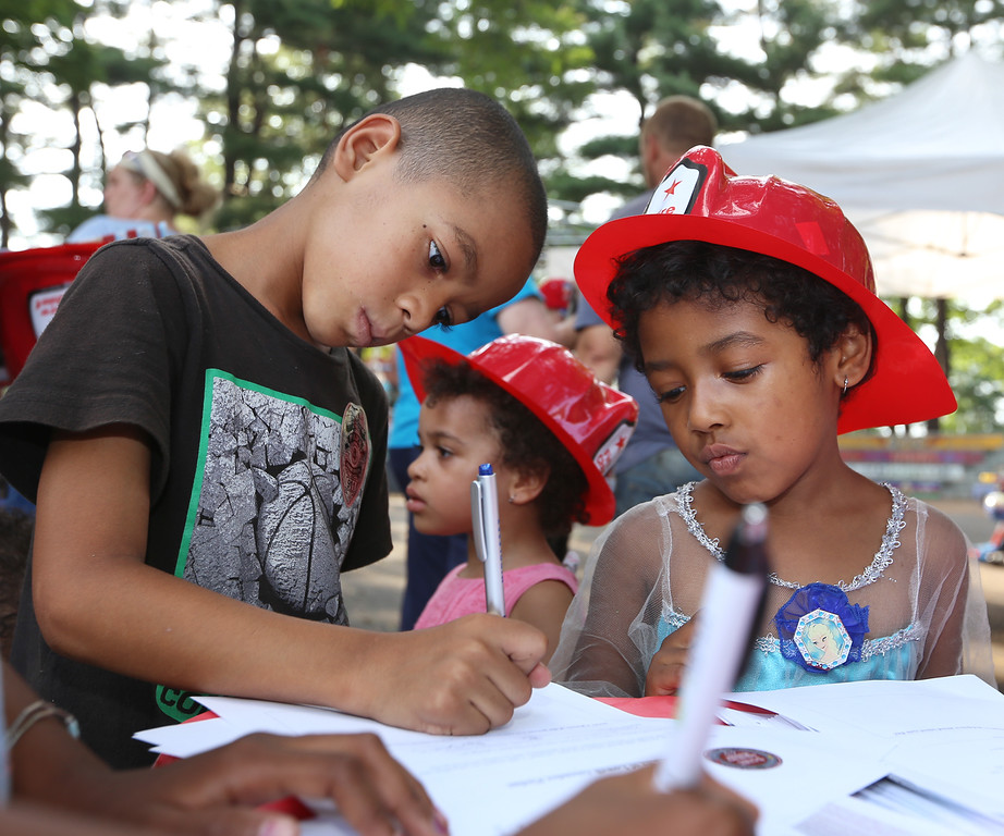 . National Night Out, at North Common, organized by the Lowell Police Department. Giovanni Williams, 7, and his sister Izzabella Williams, 5, of Lowell, fill out pledges about school attendance. At rear is their sister Brooklynn Martin, 3. (SUN/Julia Malakie)