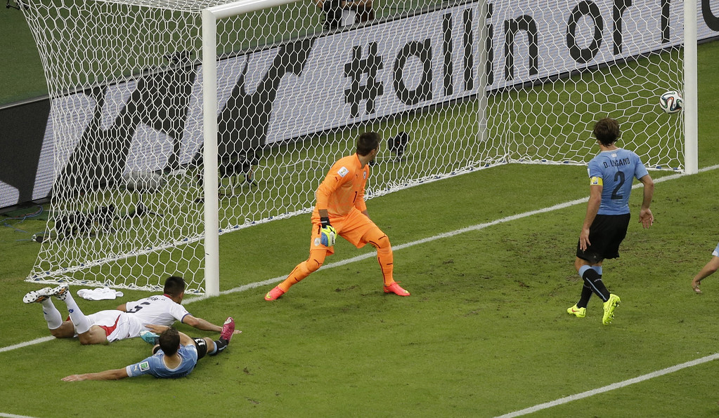 . Costa Rica\'s Oscar Duarte, left, scores his side\'s 2nd goal during the group D World Cup soccer match between Uruguay and Costa Rica at the Arena Castelao in Fortaleza, Brazil, Saturday, June 14, 2014.  (AP Photo/Sergei Grits)