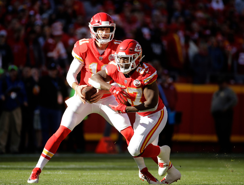 . Kansas City Chiefs quarterback Alex Smith (11) fakes a handoff to running back Kareem Hunt (27) during the first half of an NFL football game against the Oakland Raiders in Kansas City, Mo., Sunday, Dec. 10, 2017. (AP Photo/Charlie Riedel)