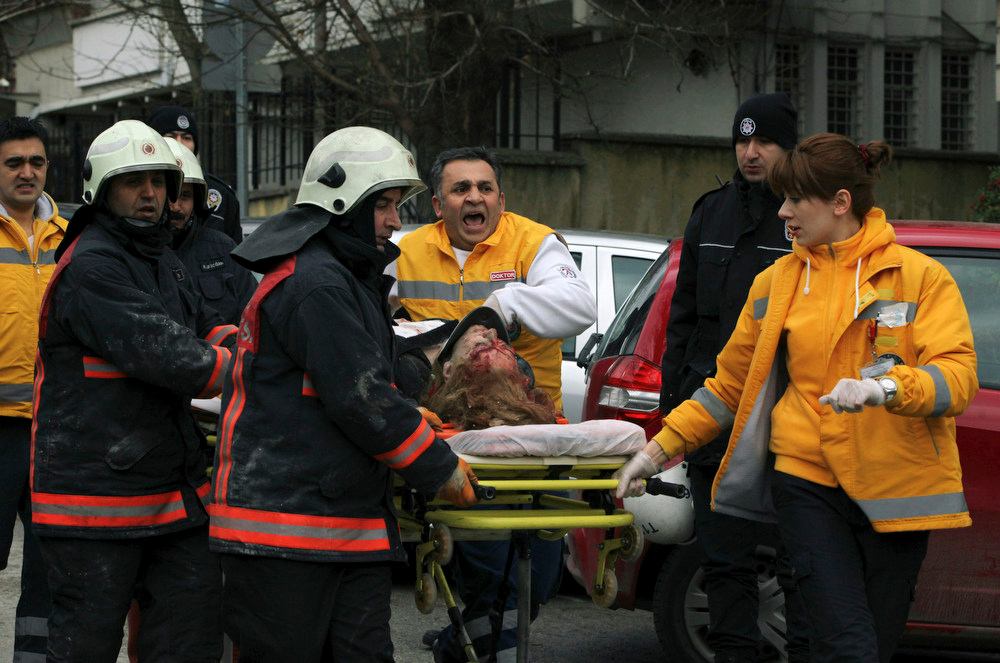 Description of . Medics carry an injured woman on a stretcher to an ambulance after a suspected suicide bomber detonated an explosive device at the entrance of the U.S. Embassy in the Turkish capital, Ankara, Turkey, Friday Feb. 1, 2013. The bomb appeared to have exploded inside the security checkpoint at the entrance of the visa section of the embassy. A police official said at least two people are dead. (AP Photo/Burhan Ozbilici)