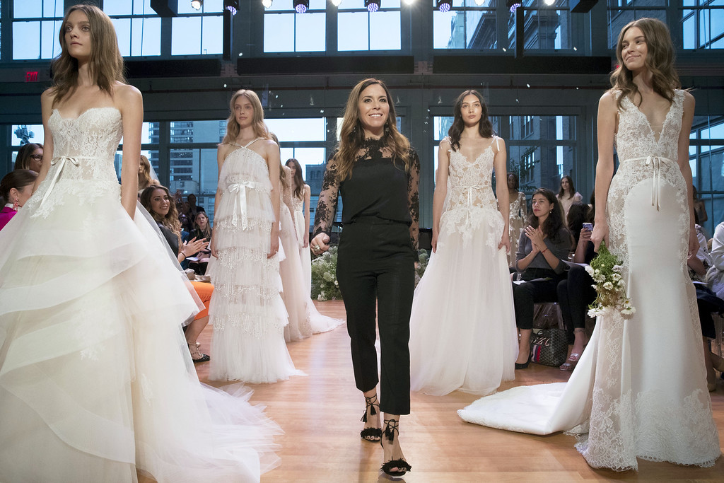 . In this Friday, Oct. 7. 6, 2016 photo, designer Monique Lhuillier, center, stands with models wearing gowns from her bridal collection during bridal fashion week in New York.  (AP Photo/Mary Altaffer)