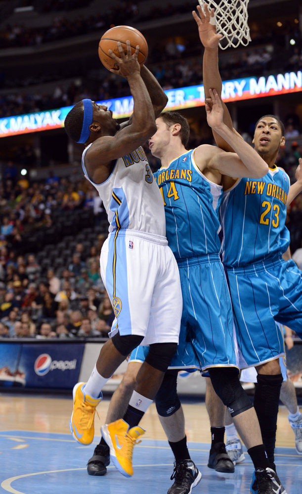 . DENVER, CO. - FEBRUARY 01: Ty Lawson of Denver Nuggets #3 jumps for the basket against Jason Smith #14 and Anthony Davis #23 of New Orleans Hornets in the 1st half of the game on February 1, 2013 at the Pepsi Center in Denver, Colorado. (Photo By Hyoung Chang/The Denver Post)
