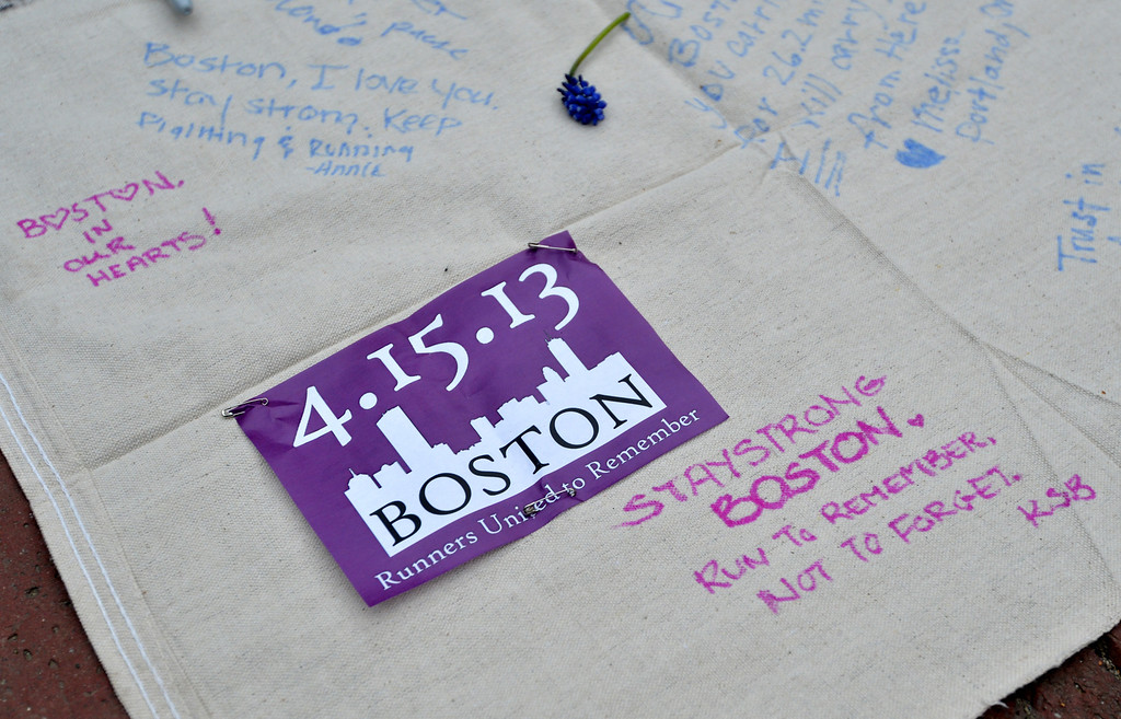 ". Messages on a banner are seen during a vigil on the Boston Common on April 16, 2013 in Boston, in the aftermath of two explosions that struck near the finish line of the Boston Marathon on April 15. Investigators said the range of suspects and motives in the grisly Boston bombings remained ""wide open\"" as experts assessed remnants of the crude devices designed to inflict maximum suffering.    STAN HONDA/AFP/Getty Images"