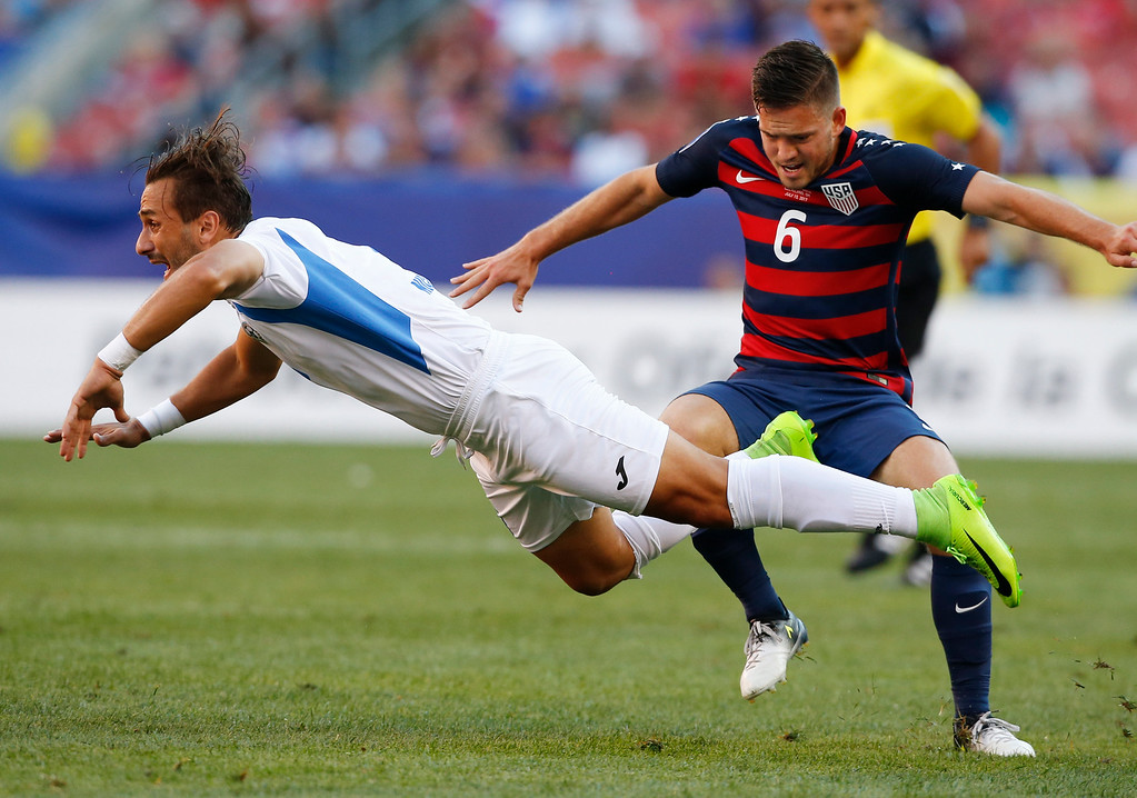 . Nicaragua\'s Daniel Candena (9) is tripped by United States\' Kelyn Rowe (6) during a CONCACAF Gold Cup soccer match in Cleveland, Saturday, July 15, 2017. (AP Photo/Ron Schwane)
