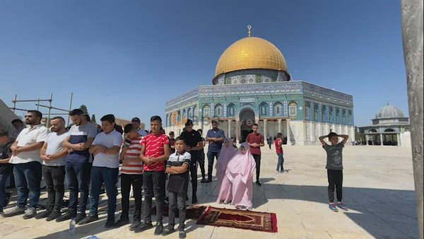 Palestinian Muslims attend Friday prayer in front of the Dome of the Rock Mosque