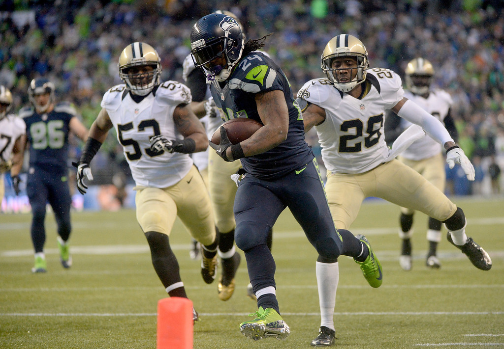 . SEATTLE, WA - JANUARY 11:  Running back Marshawn Lynch #24 of the Seattle Seahawks scores a 31-yard touchdown run against the New Orleans Saints in the fourth quarter during the NFC Divisional Playoff Game at CenturyLink Field on January 11, 2014 in Seattle, Washington.  (Photo by Harry How/Getty Images)