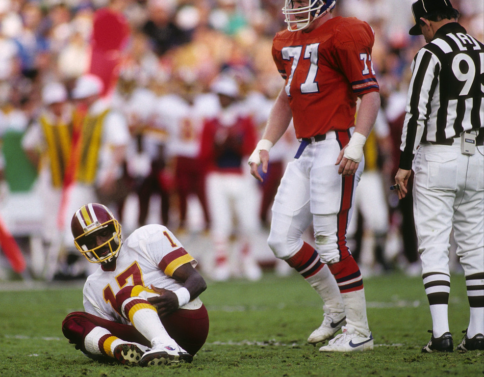 . Quarterback Doug Williams #17 of the Washington Redskins goes down in pain in front of defensive end Karl Mecklenburg #77 of the Denver Broncos during Super Bowl XXII at Jack Murphy Stadium on January 31, 1988 in San Diego, California.  The Redskins won 42-10.  (Photo by George Rose/Getty Images)