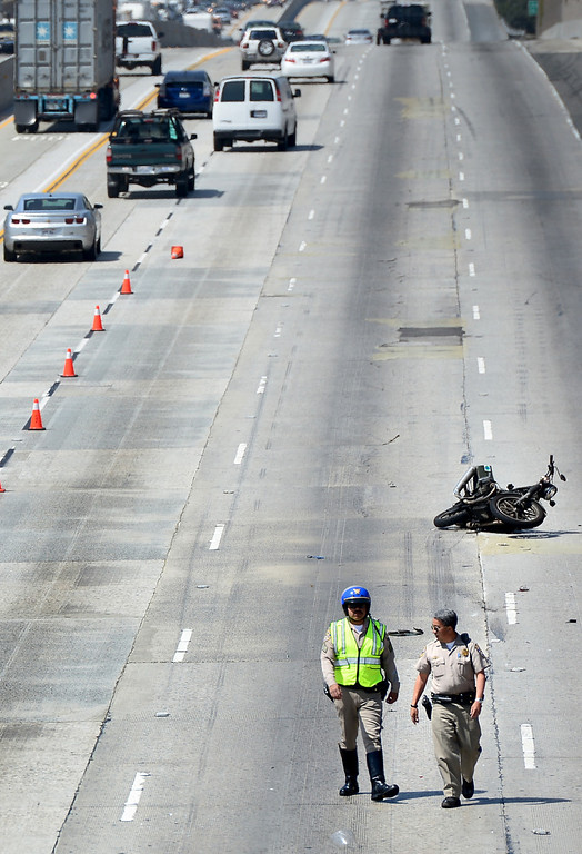 . California Highway Patrol officers investigate a fatal motorcycle crash on the westbound 60 Freeway east of Hacienda Boulevard in Hacienda Heights Tuesday, March 26, 2013.(SGVN/Staff Photo by Sarah Reingewirtz)