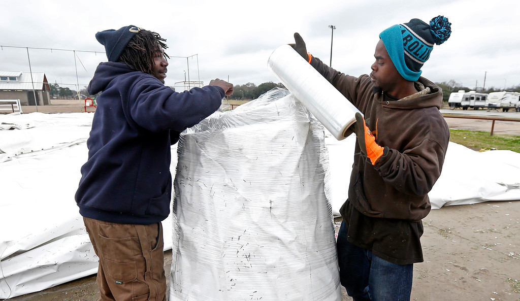 . Malcolm Strong, right and Jarquris McCullum, both of Jackson, Miss., brave the brisk wind and cold temperatures, to wrap up one of the five 60x100 ft. tent sections that made up the Jackson Giant Tree Company on the Mississippi State Fairgrounds in Jackson, Miss., Wednesday, Dec. 27, 2017. A crew of six employees erected the Christmas tree emporium before Thanksgiving, manned the operation and then took down the facility after Christmas. (AP Photo/Rogelio V. Solis)
