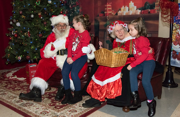 12/06/18 Wesley Bunnell | Staff Plainville held a tree lighting ceremony on Thursday at Fire HQ featuring singing, refreshments and a visit from Santa with a chance to sit on his lap. Gonna Agudelo, age 9, sits on Santa's lap while sister Kailyn, age 6, sits with Mrs. Clause.