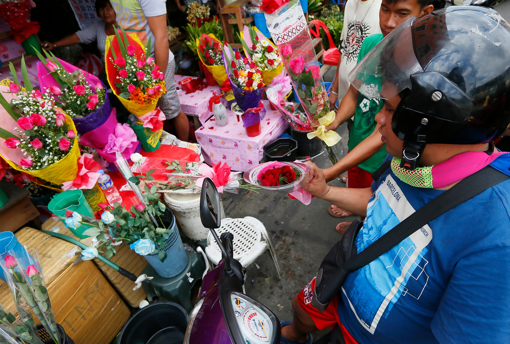 . A motorist buys a bouquet of roses as Filipinos celebrate Valentine\'s Day, Tuesday, Feb.14, 2017, in Manila, Philippines. Valentine\'s Day, associated with love and romance, oftentimes are expressed with flowers, chocolates, balloons and dinner dates. (AP Photo/Bullit Marquez)