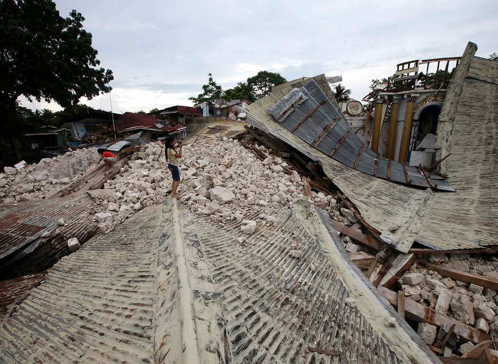 . Residents take photos of the rubble of Our Lady of Light church at Loon township, Bohol province in central Philippines Thursday Oct.17, 2013. (AP Photo/Bullit Marquez)